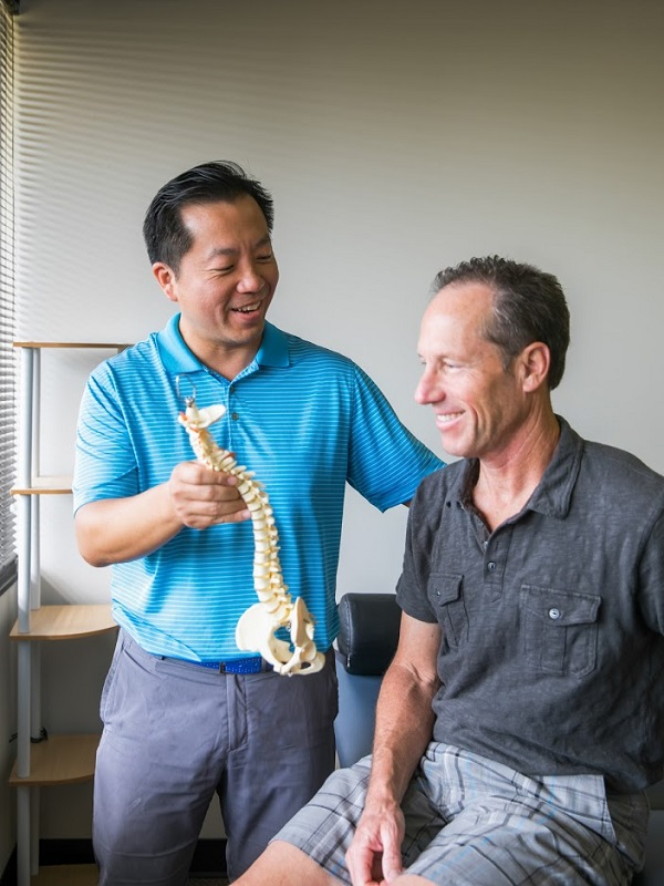 Doctor Lin teaching spinal issues to patient