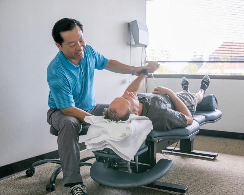 Dr. Lin adjusting patients arm